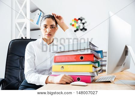 Exhausted tired businesswoman sitting at the office desk and looking at camera