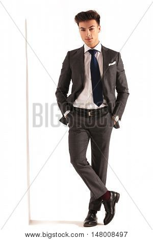 sexy young business man with hands in pockets standing near wall in studio