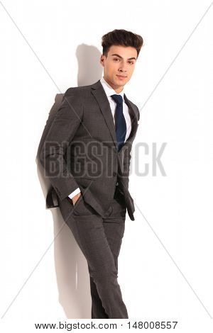relaxed young business man in grey suit standing against wall with hands in pockets