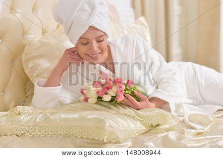 beautiful young woman wearing a white bathrobe  with flowers