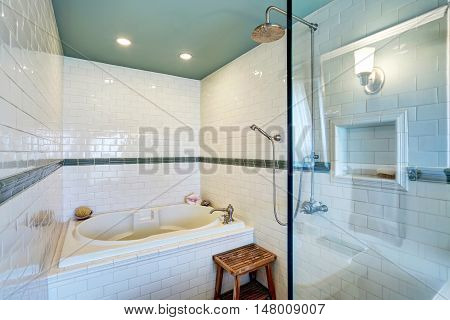 Blue Bathroom Interior With White Tile Trim Wall, Glass Cabin Shower And Bath Tub.
