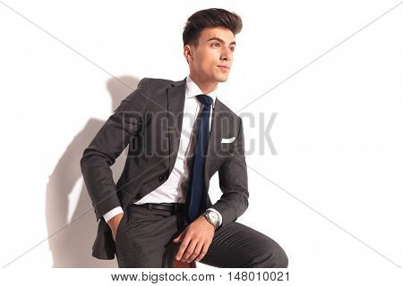 side view of a business man sitting and looking away from the camera on white background