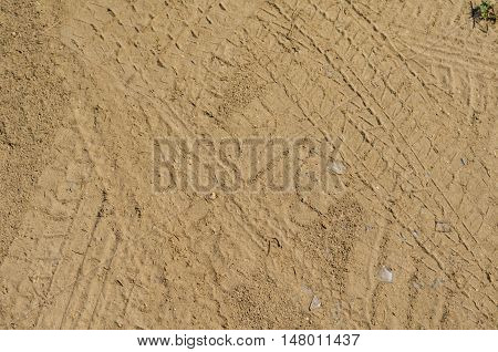 Texture of yellow sand with marks of car tyres and foot prints