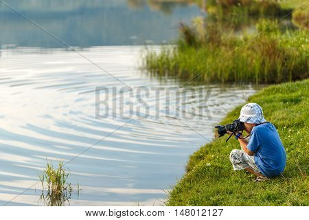 School-age boy photographing lake taking a picture