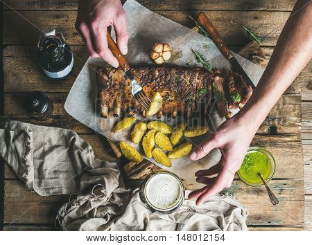 Man eating roasted pork ribs with garlic, rosemary and green herb sauce on rustic wooden table. Man' s hand holding fork with fried potato and reaching for glass of dark beer, top view