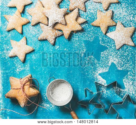 Christmas or New Year holiday food background. Sweet gingerbread cookies in shape of star with sugar powder in sieve and metal shapes on bright blue painted plywood background, top view, copy space