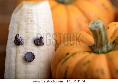 pumpkins and ghosts made with banana and chocolate for halloween over wood