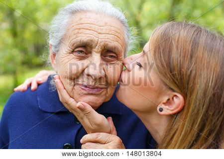 Picture of a senior woman with her caring granddaughter