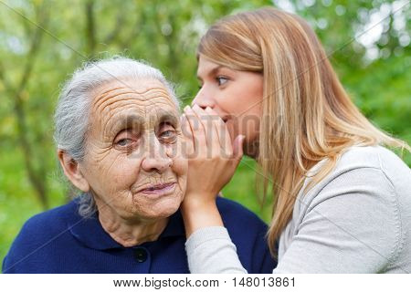 Picture of a young happy female whispering in her grandmother's ear