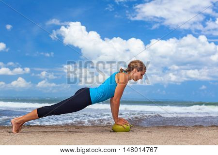 Woman fitness exercise plank on raw green coconut to keep fit and health. Ocean beach surf background. Healthy lifestyle morning workout sport activity on summer family holiday in tropical island.