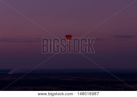 Heart shaped air balloon flying over amazing landscape at sunset