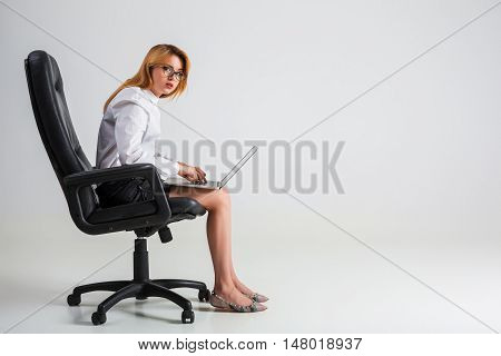 young woman sitting on the chair and using laptop. tired businesswoman under the weight of hard work. hunchbacked