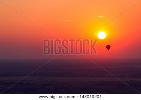 Hot air balloon flying over amazing landscape at sunset
