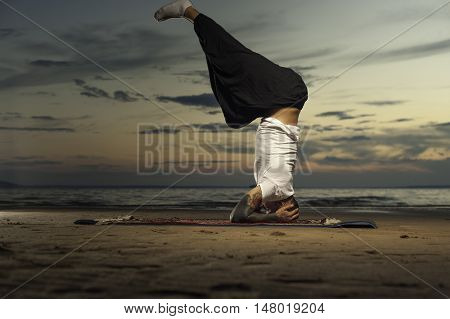 Young tattoo man practicing high level yoga on the beach at sunset. Headstand or shoulderstand practicing. Full length shot.