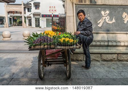 Shanghai China - October 23 2013: Vendor is selling fruits on the street with her cart in Shanghai China.