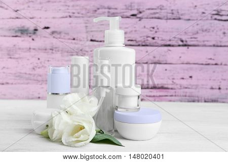 Different cosmetic bottles and eustoma flowers on purple wooden background