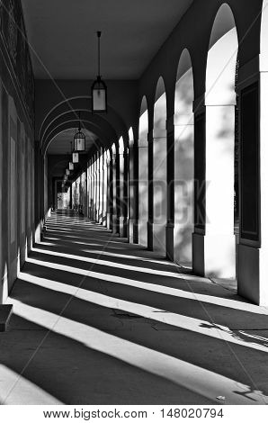 Long Arcade in Munich Germany. Classical gallery with contrasting geometric shadows in perspective. Black and white.
