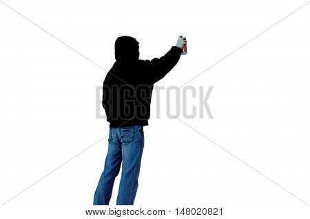 Artist with can of spray paint draws graffiti picture isolated on a white background in black hood unknow back view