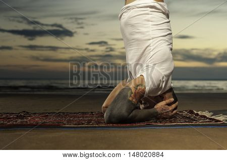 Cropped shot of Young tattoo man doing advanced yoga exercise on the beach at sunset. Practicing head or shoulders stand outdoors.