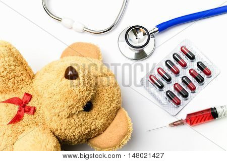 Doctor work table white background desk with medical blister of red and black capsule red injection syringe stethoscope and brown teddy bear. Children medical concept.