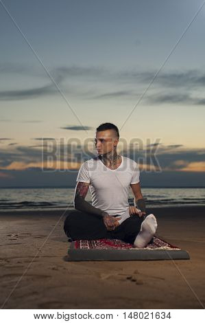 Attractive young man with tattoos sitting on the beach at sunset and practicing yoga. Full length shot.