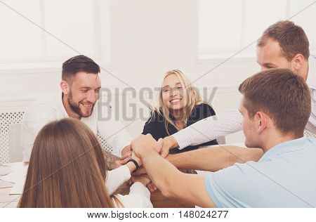 Team put hands together, show connection and alliance. Teambuilding in office, young happy businessmen and women in casual unite hands for teamwork and cooperation at new project.