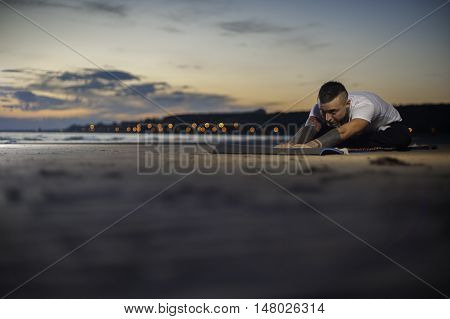 Young flexible caucasian man with tattoos on the body practicing yoga on the beach at sunset.