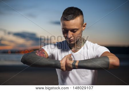 Young caucasian man with tattoos doing yoga and meditating on the beach at sunset.