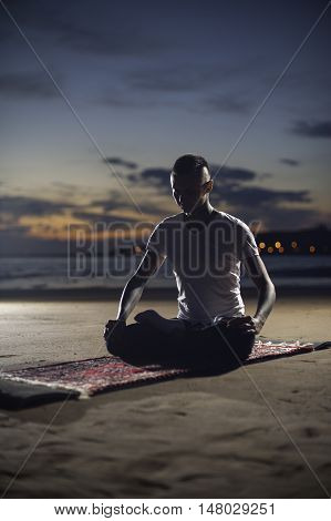 Young calm man sitting on the beach at sunset and meditating. Yoga exercising, lotus pose.