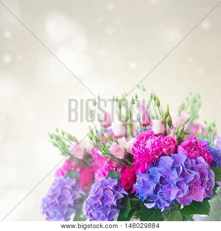 Bright pink peony, eustoma and blue hortensia flowers bouquet on gray bokeh background