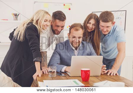 Happy smiling business people group look attentive at laptop in the office. Successful corporate team of female and male coworkers check internet site of company together, partners and colleagues.