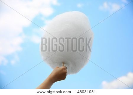 Female hand holding cotton candy on blue sky background
