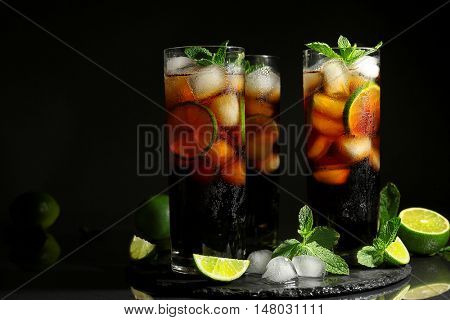Cuba libre cocktails with mint, ice and lime on dark background