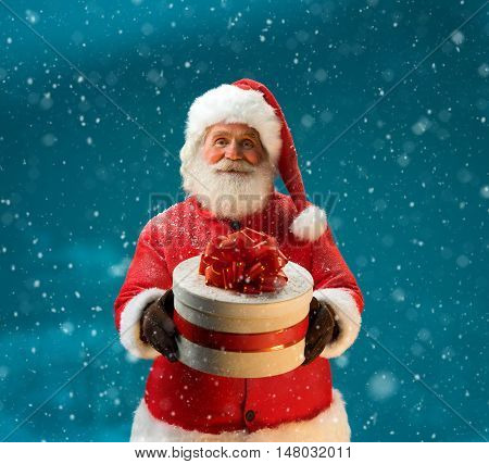 Santa Claus in snowfall with gifts to children. Merry Christmas & New Year's Eve concept. Close up on blurred blue background. Copy space.