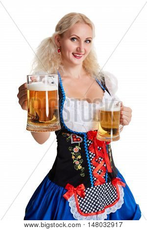 Beautiful young blond girl in dirndl drinks out of oktoberfest beer stein. Isolated on white background. she holds a glass with a drink and smiling. focus on the glass