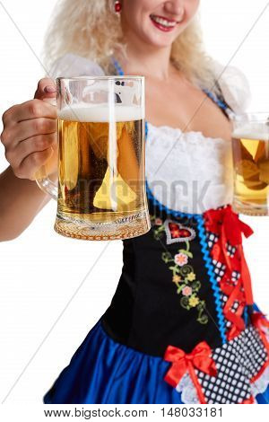 Beautiful young blond girl in dirndl drinks out of oktoberfest beer stein. Isolated on white background. she holds a glass with a drink and smiling. close-up