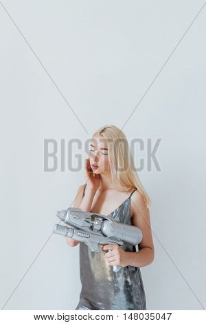 Close up portrait of a beautiful fashion blonde girl in silver shiny dress holding water gun and posing with eyes closed isolated on the grey background