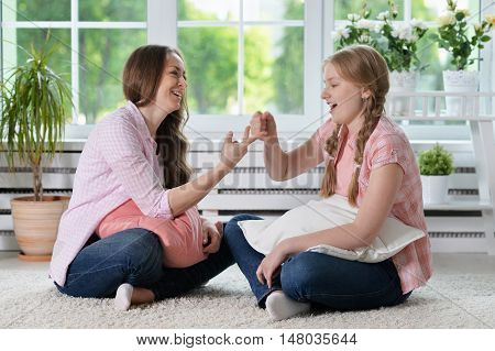 portrait of happy mother and  daughter having fun at home