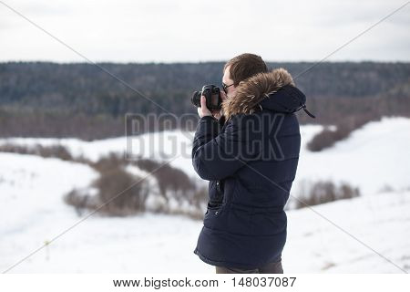 Photographer photographing winter panorama in hilly plain