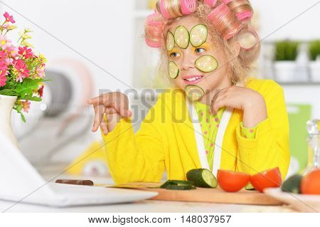 Happy cute little girl in hair curlers with laptop and vegetables