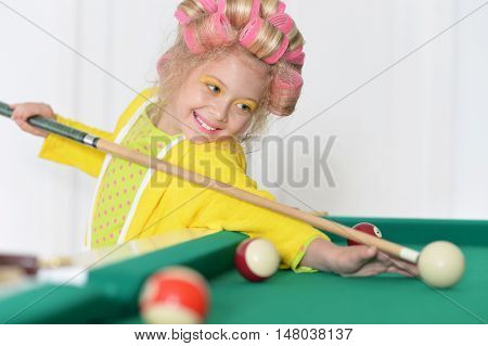 Cute little girl  in hair curlers playing billiard