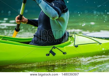 Recreational Lake Kayaking Closeup Photo. Kayak Paddling in Action. Water Sports Theme.
