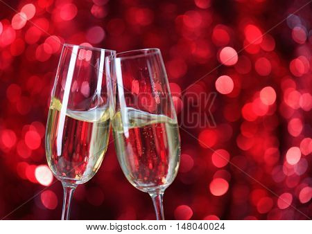 Two glasses of champagne   against  red background with sparkles. Very shallow depth of field. Selective focus