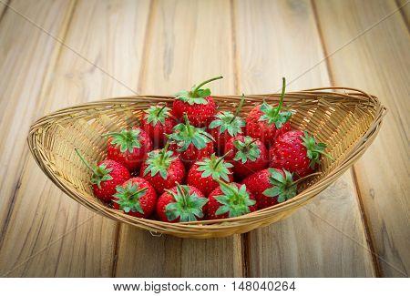 Strawberry in basket on teak wood background.