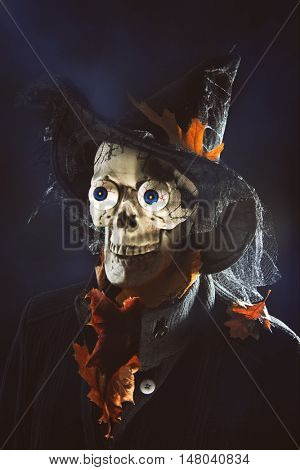 Halloween man covered in autumn leaves and spiders with witches hat