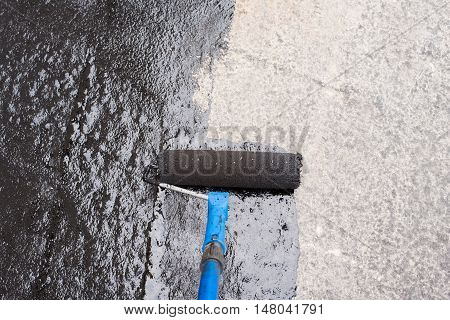 Roller brush. Worker covered surface bitumen primer for improving adhesion during surfacing rolled waterproofing during the installation of isolation on industrial or household objects