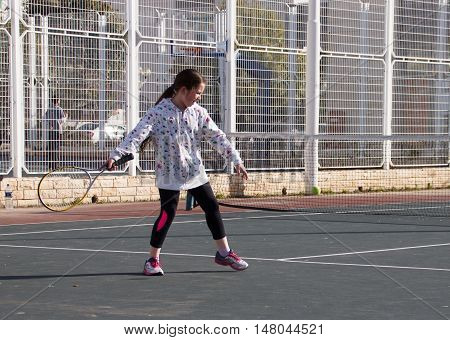 Nahariya, Israel, February 13 2016: Girl playing tennis on the court and hits the racket on the ball in Nahariya, Israel