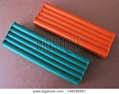 Plasticine on brown paper. Plasticine on brown background. Green plasticine. Orange plasticine. Plasticine on colored paper. The plasticine on the paper background. Modeling clay. School supplies. Supplies for creativity.
