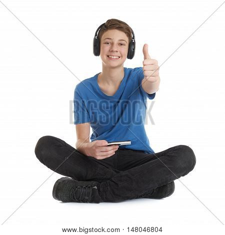 Cute teenager boy with smart phone in hands in blue T-shirt, headphones and lotus posture over white isolated background