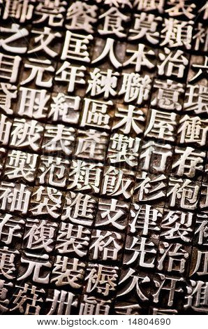 A vertical arrangement of random Chinese type and character symbols, shallow depth of field. Mixed both new and well worn characters.